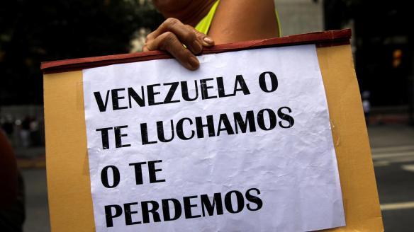 Una mujer sostiene un cartel en una protesta contra el presidente Maduro...