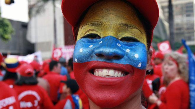 Mujer con la bandera de Venezuela pintada en su rostro.