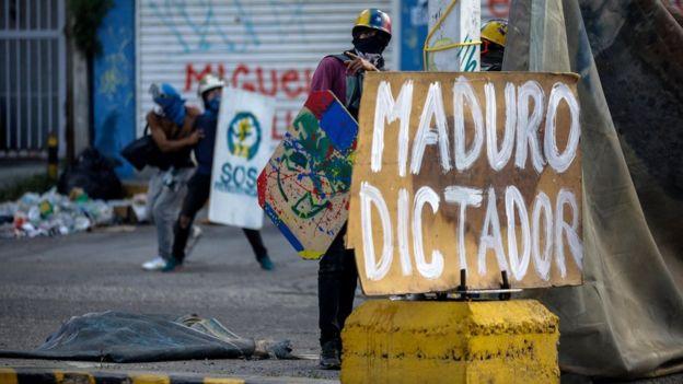 Manifestante con una pancarta que dice